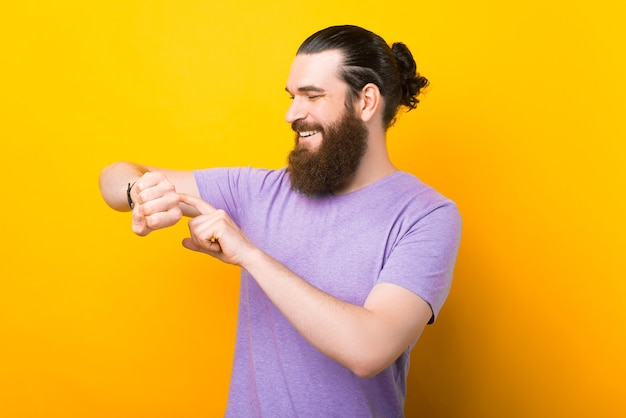 Homem barbudo caucasiano está verificando seu relógio inteligente sobre fundo amarelo.