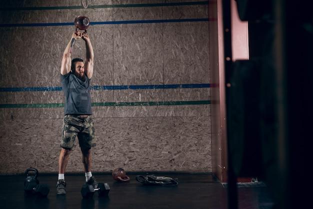 Homem barbudo caucasiano musculoso levantando kettlebells no ginásio crossfit.