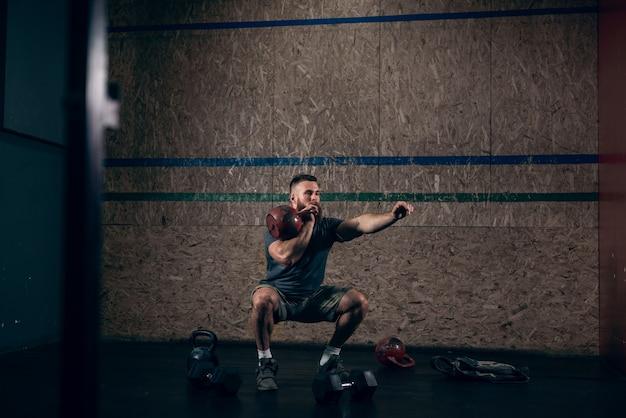 Homem barbudo caucasiano musculoso levantando kettlebells no ginásio.