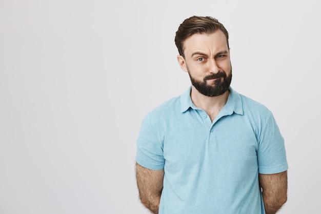 Homem barbudo cético a apertar os olhos e parecer insatisfeito