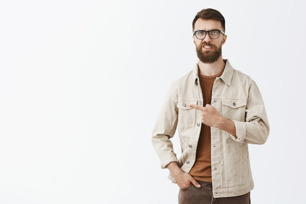 Homem barbudo cético e desapontado em óculos posando contra a parede branca