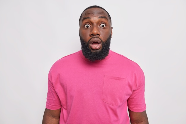 Homem barbudo chocado com olhos esbugalhados de admiração olha impressionado e sem palavras ouve boato chocante e impressionante veste uma camiseta rosa básica isolada sobre uma parede branca