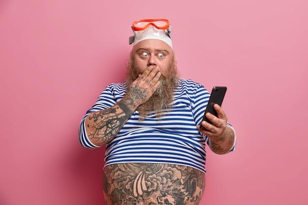 Homem barbudo chocado e robusto cobre a boca e encara o smartphone, lê algo surpreendente, vestido com camisa de marinheiro, óculos de natação e barriga tatuada