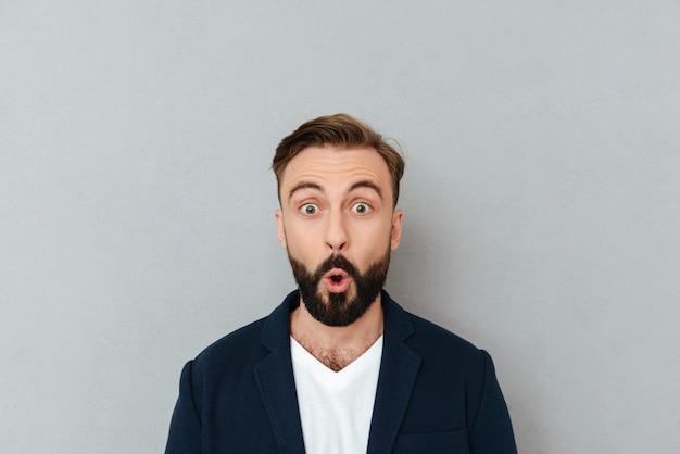Homem barbudo chocado em roupas de negócios, olhando para a câmera sobre cinza