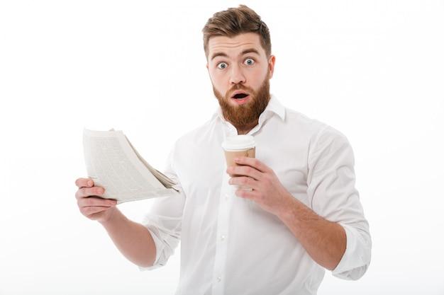 Homem barbudo chocado em roupas de negócios, segurando o jornal