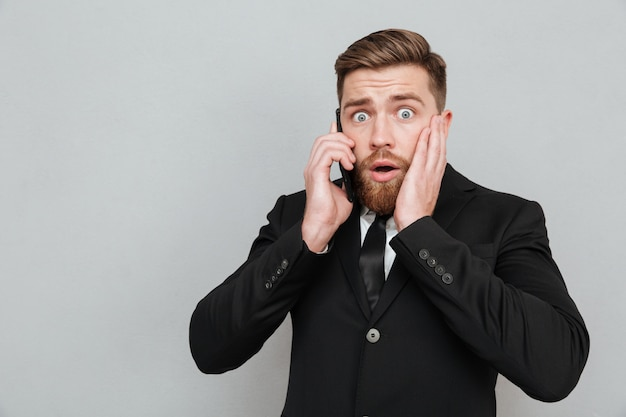 Homem barbudo chocado falando em seu smrtphone com a boca aberta