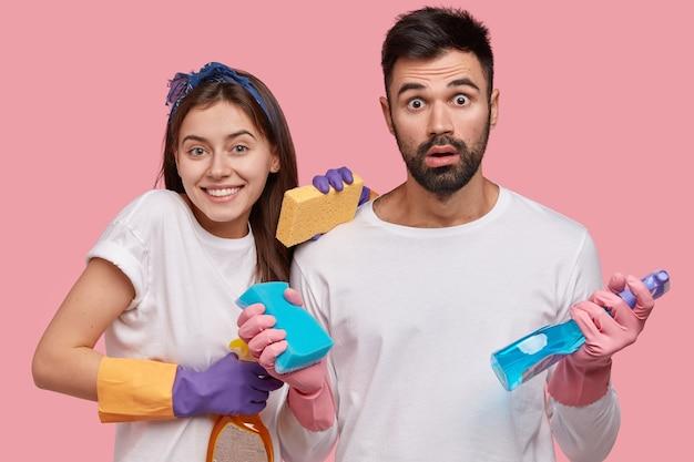 Homem barbudo chocado, jovem bonita e positiva usa material de limpeza para arrumar o quarto, faz trabalhos domésticos durante o dia de folga