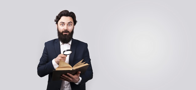 Homem barbudo chocado lendo livro com lupa, homem sobre parede cinza, maquete panorâmica com espaço para texto