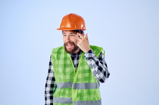 Homem barbudo colete verde capacete laranja fluxo de trabalho estúdio de gestos com as mãos