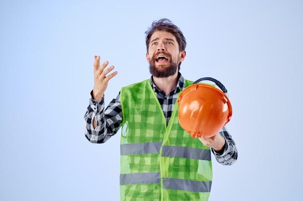Homem barbudo colete verde capacete laranja fluxo de trabalho gestos com as mãos fundo azul