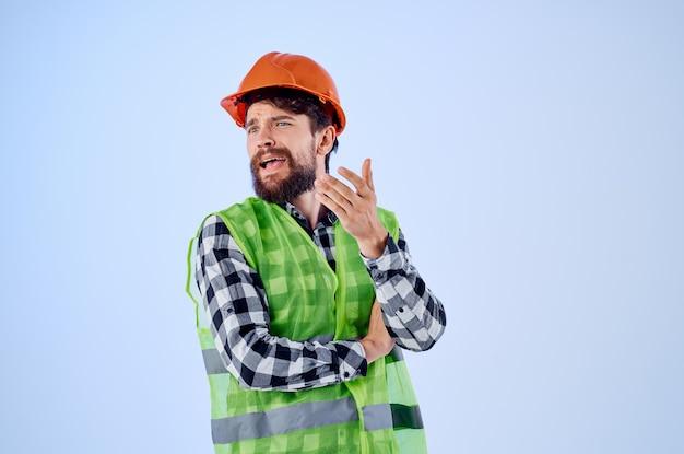 Homem barbudo colete verde capacete laranja fluxo de trabalho gestos com as mãos fundo isolado