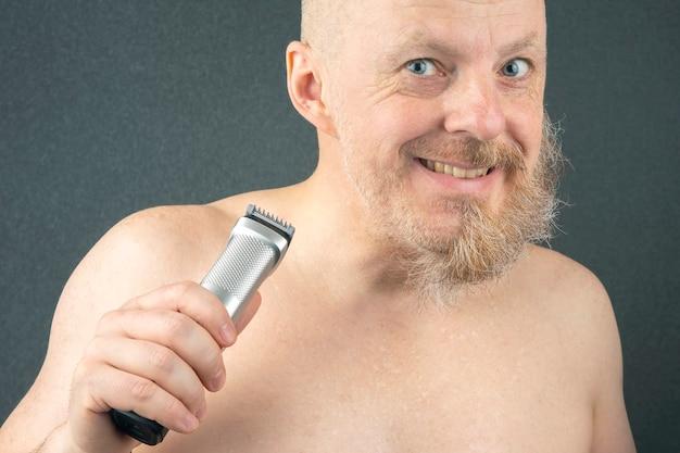 Homem barbudo com aparador para ajustar a barba na mão. barbearia e barbearia elegante