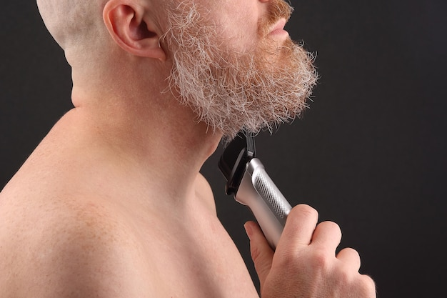 Homem barbudo com aparador para ajustar a barba na mão