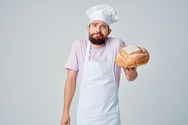 Homem barbudo com avental branco cozinhando pão