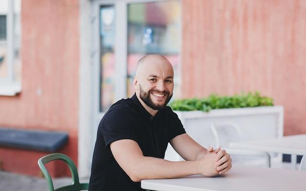 Homem barbudo com barba sorrindo enquanto está sentado com uma camiseta em um café de rua