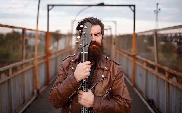 Homem barbudo com bigode comprido e jaqueta de couro marrom cobrindo o rosto com um violão