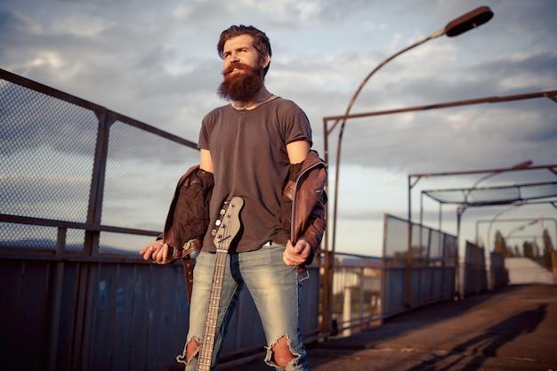 Homem barbudo com bigode comprido tirou a jaqueta de couro marrom e segura uma guitarra elétrica no fundo de uma ferrovia