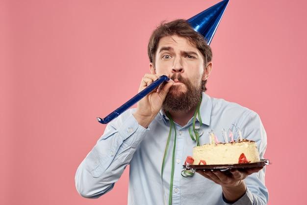 Homem barbudo com bolo na visão recortada de emoções de fundo rosa. foto de alta qualidade