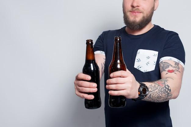 Homem barbudo com braços tatuados segurando garrafas de cerveja