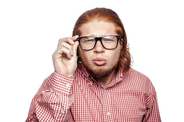 Homem barbudo com cabeça de leitura pensando, camisa vermelha e sardas segurando óculos e olhando para a câmera