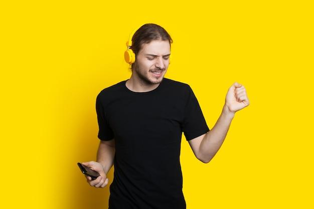 Homem barbudo com cabelo comprido dançando e ouvindo música em fones de ouvido na parede amarela de um estúdio