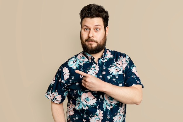 Homem barbudo com camisa floral de verão apontando para o lado