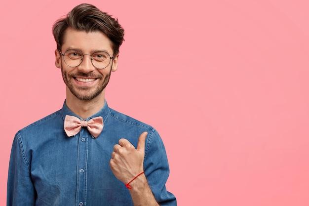 Homem barbudo com camisa jeans e gravata borboleta rosa