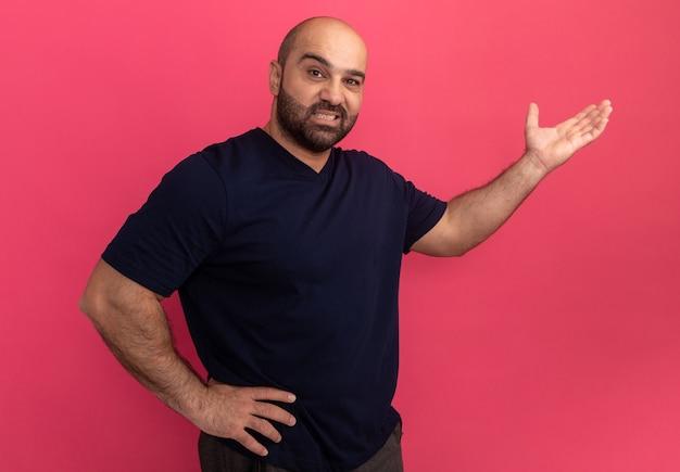 Homem barbudo com camiseta azul marinho confuso apresentando espaço da cópia com o braço da mão em pé sobre a parede rosa