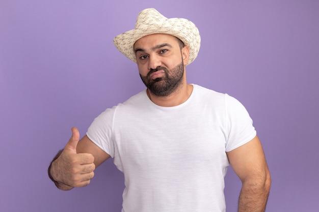 Homem barbudo com camiseta branca e chapéu de verão com expressão confiante mostrando os polegares em pé sobre a parede roxa