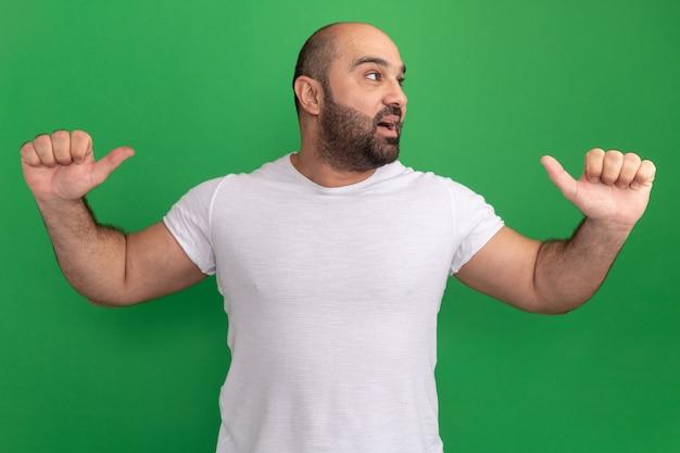 Homem barbudo com camiseta branca olhando para o lado com uma cara feliz sorrindo apontando para si mesmo em pé sobre a parede verde