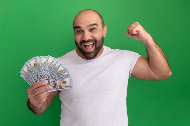Homem barbudo com camiseta branca segurando dinheiro feliz e animado levantando o punho em pé sobre a parede verde