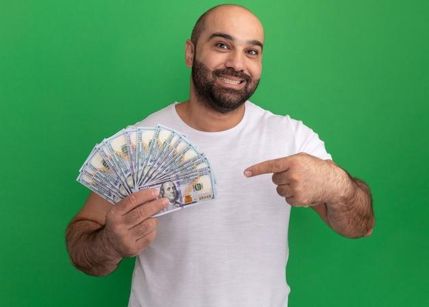 Homem barbudo com camiseta branca segurando dinheiro, feliz e positivo, sorrindo alegremente apontando com o dedo indicador para o dinheiro em pé sobre a parede verde