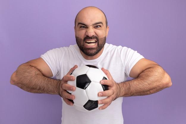 Homem barbudo com camiseta branca segurando uma bola de futebol com cara de zangado gritando enlouquecendo de pé sobre a parede roxa