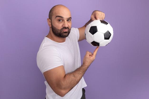 Homem barbudo com camiseta branca segurando uma bola de futebol no dedo e rosto sério em pé sobre a parede roxa