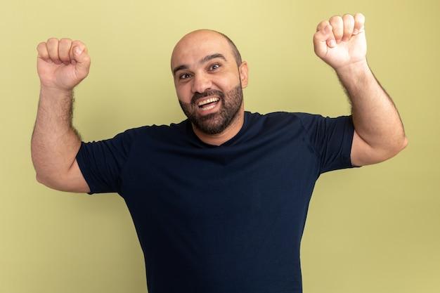 Homem barbudo com camiseta preta louco, feliz e animado, gritando com os punhos cerrados e regozijando-se com seu sucesso em pé sobre a parede verde