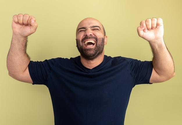 Homem barbudo com camiseta preta louco, feliz e animado, gritando com os punhos cerrados em pé sobre a parede verde