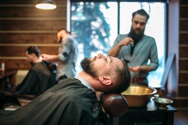 Homem barbudo com capa de salão na barbearia
