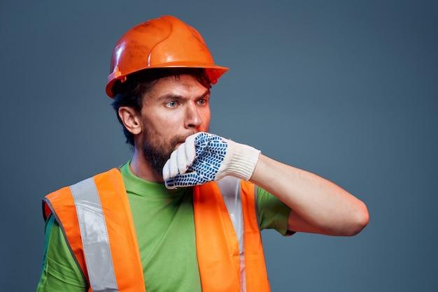 Homem barbudo com capacete laranja luvas profissionais