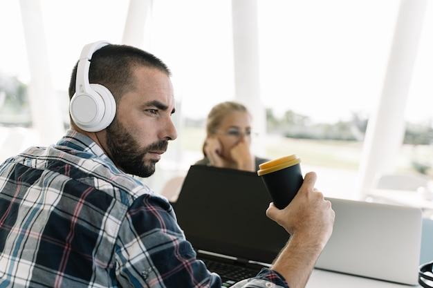 Homem barbudo com capacetes brancos e um café na mão, sentado na frente de um laptop em um coworking