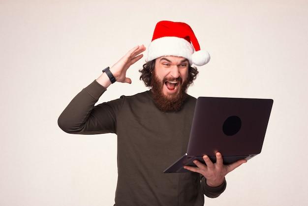 Homem barbudo com chapéu de natal está surpreso com o laptop.