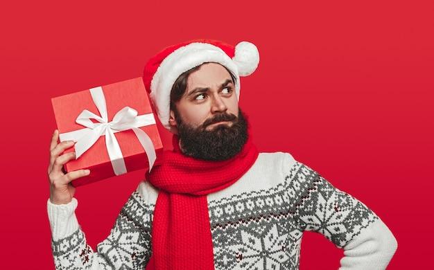 Homem barbudo com chapéu de papai noel e suéter agitando presente embrulhado