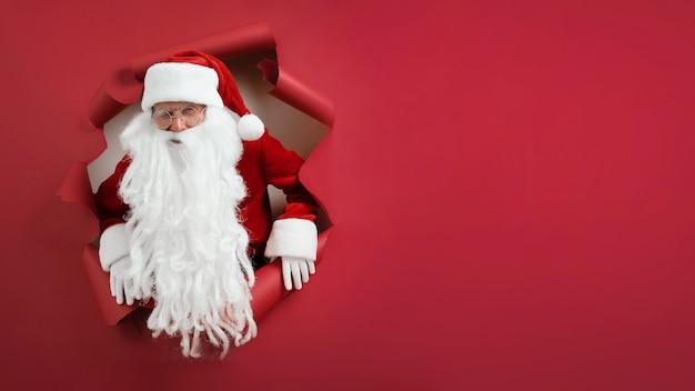 Homem barbudo com chapéu de papai noel pisca os olhos e olha pelo buraco no papel vermelho.