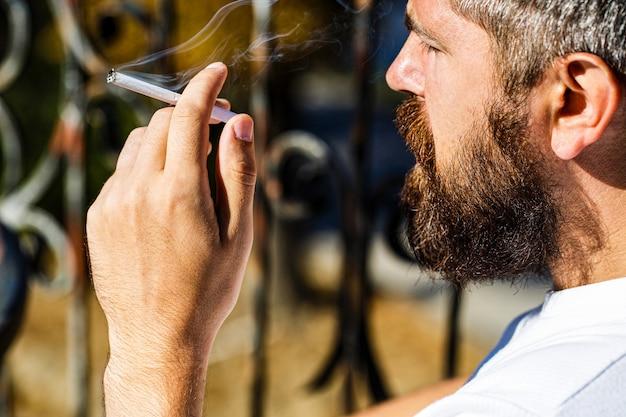 Homem barbudo com charuto. homem de barba e bigode fumam charuto.