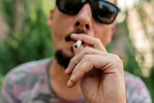 Homem barbudo com cigarro