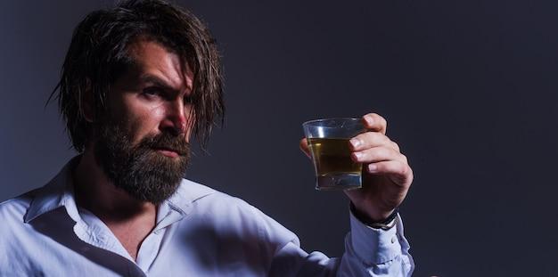 Homem barbudo com copo de uísque. bebida cara. macho bebendo conhaque ou conhaque. degustação, degustação.