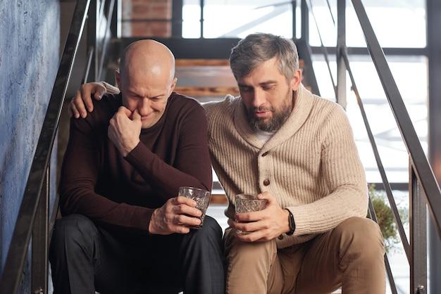 Homem barbudo com copo de uísque sentado na escada e abraçando o amigo enquanto o apóia em situação difícil