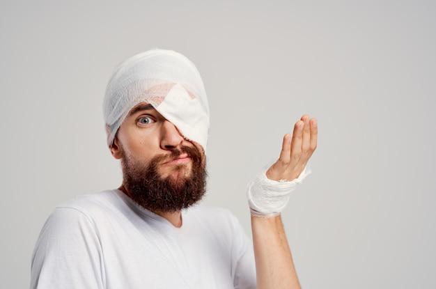Homem barbudo com curativo na cabeça e nos olhos, medicamento hospitalar para hospitalização