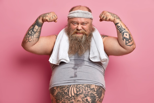 Homem barbudo com excesso de peso e motivado levanta os braços, mostra os músculos após o treino, quer ser forte e ter bíceps, leva um estilo de vida saudável, tem programa de condicionamento físico para emagrecimento, fé em si mesmo.