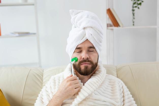 Homem barbudo com ferramenta de massagem facial. cuidados com a pele masculina e conceito de spa.