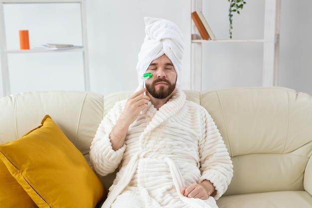 Homem barbudo com ferramenta de massagem facial, cuidados com a pele masculina e conceito de spa
